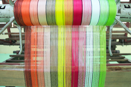 handloom: Colorful yarn pattern is set up on the loom bench and ready to weave.