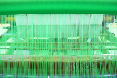 handloom: Green yarn pattern is set up on the loom bench and ready to weave. Stock Photo