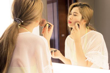 removing make up: Beautiful Asian teenage girl applying powder her cheek before the mirror in bathroom Stock Photo