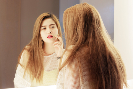 removing make up: Beautiful Asian teenage girl touching her face before the mirror in bathroom Stock Photo