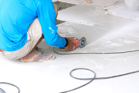 tile cutter: Industrial tiler builder worker working with floor tile cutting equipment Stock Photo