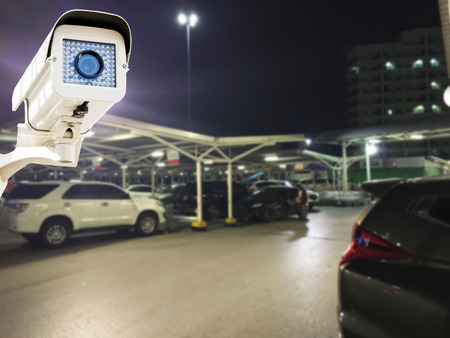 customer records: The CCTV Security Camera operating in parking lot car at night time blur background.