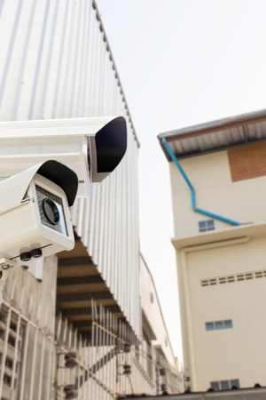 electronic survey: The CCTV Security Camera operating on backyard roofing house  blur background. Stock Photo