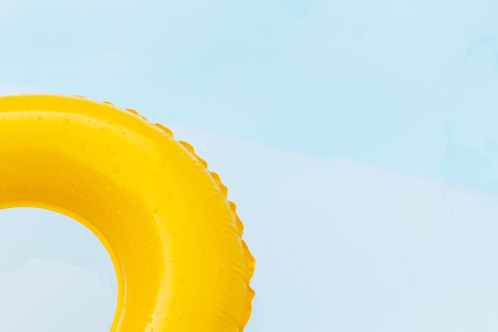 flotation: Close up yellow ring floating in refreshing blue swimming pool. Stock Photo