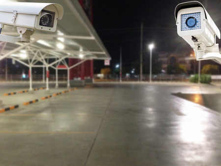 parking lot interior: The CCTV Security Camera operating in parking lot car at night time blur background.