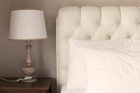 White pillow on white luxury bed in bedroom, effect color, sepia style.