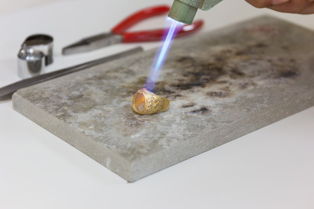 endoscopic: Gold ring hand craft on stone, gold ring, gold bar, gold goldsmith, gold accessory, gold treasure, gold pendant, gold ornament, gold golden background.