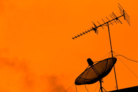 Television antenna and satellite dish for communication broadcast on the roof with sunset sky, twilight time, silhouette orange background, effect light, with copy space.