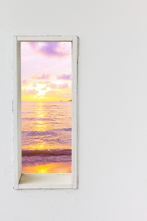 beach window: White wall window with sunset sea beach view, vertical landscape concept background.