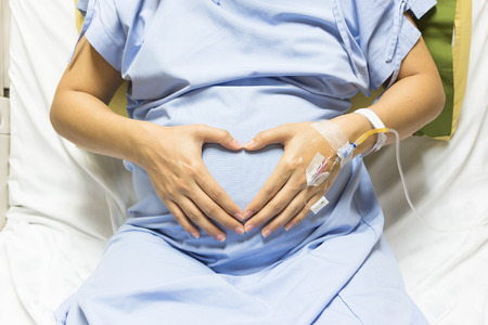 Asian Pregnant Woman patient is hands shaped heart drip receiving a saline solution on bed VIP room at hospital, selective focus. Stockfoto