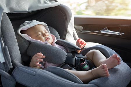 Close Up asiática dormir lindo bebé recién nacido en el asiento del coche moderno. Niño recién nacido que viaja seguridad en la carretera. Forma segura de viajar abrochado el cinturón de seguridad en un vehículo con niños pequeños. Viaje con un bebé.