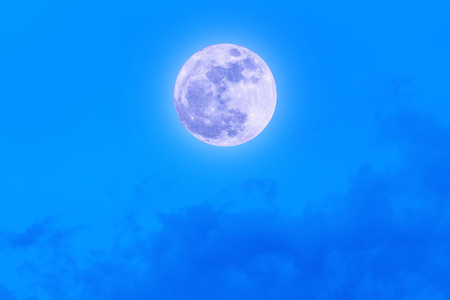 The Moon at it largest also called supermoon with blue sky and clouds. Stock Photo