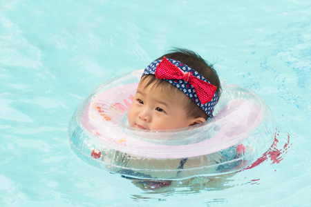 Asian cute eight month baby playing swimming pool, Active healthy first time playing swim in pool at home.