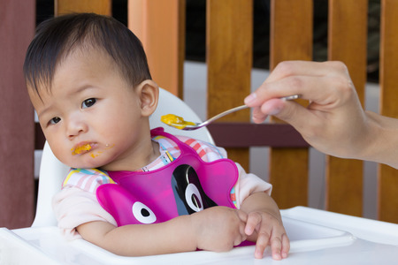Asian cute baby boring eat food, Mother feeding solid food for young kid eight month.