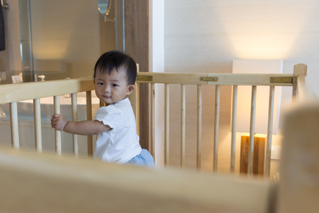 Asian cute baby standing on baby cot in luxury bed room hotel.