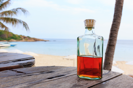 Beverage alcohol is brandy bottle on wood table at sea beach background.
