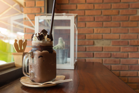 Dark chocolate milk shake with whipped cream brownie on wood table, window cafe background, beverage summer.