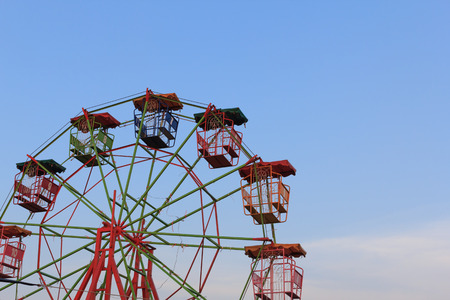 Vintage ferris on blue sky background, at carnival park.