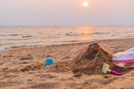 Sand and toys on the beach background, sunset time in the sea, summer beach concept. Stock Photo