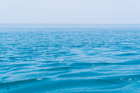 Beautiful  smooth ocean water and blue sky background, landscape sea and ocean concept.