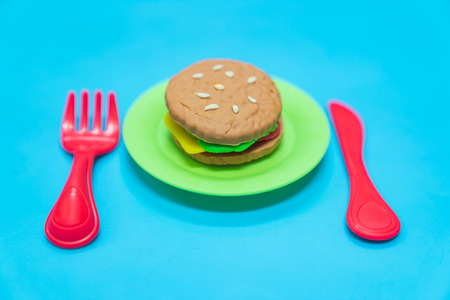 Fastfood model with hamburger chesse on plastic blue table background, play dought at home, child care cooking food model, educational toys for kid creative for toddlers concept. Stock Photo