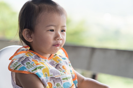 Close up Asain cute baby girl eatting ice water on white chair. Stock Photo