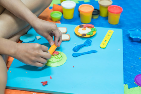 Parent having fun playing colorful modeling clay, play dought at home, child care cooking food model, educational toys for kid creative for toddlers concept.
