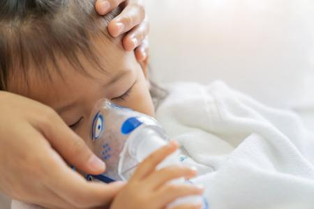 Asiatische Babymädchen-Atembehandlung mit Mutter kümmern sich, im Raumkrankenhaus, schließen nahes Gesundheitskindkonzept sonnigen hellen Hintergrund. Standard-Bild