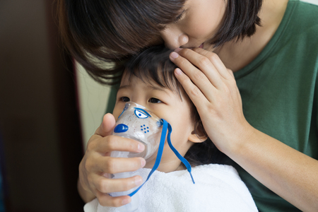 Asian baby girl breathing treatment with mother take care, at room hospital, close up health care kid concept sunny light background. Stock Photo - 102668830