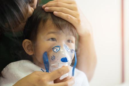 El tratamiento de respiración de la niña asiática con la madre cuida, en el hospital de la habitación, cerca del fondo claro soleado del concepto del niño de la atención médica.