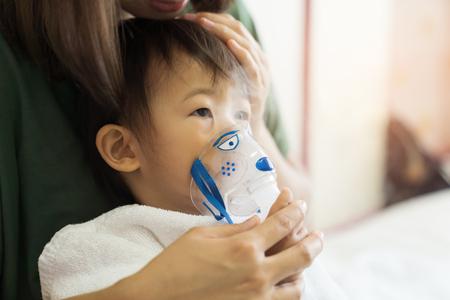 El tratamiento de respiración de la niña asiática con la madre cuida, en el hospital de la habitación, cerca del fondo claro soleado del concepto del niño de la atención médica