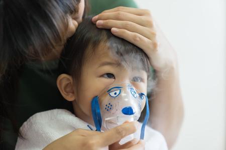 El tratamiento de respiración de la niña asiática con la madre cuida, en el hospital de la habitación, cerca del fondo claro soleado del concepto del niño de la atención médica Foto de archivo