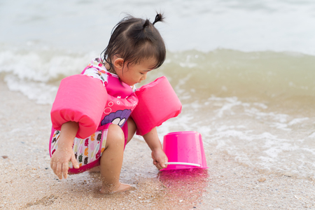 Asian baby girl playful on the beach background, vacation holiday sea concepts.
