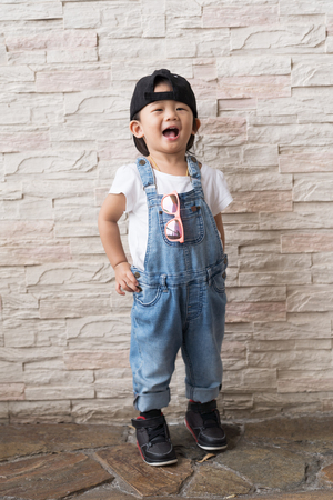 Asian cute baby kid happiness on the white brick wall background, portrait child concepts. Stock Photo
