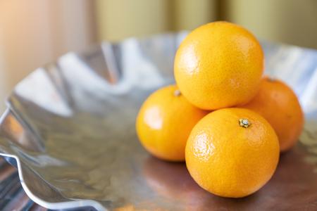 Close up fresh orange fruits on luxury dish background. Stock Photo