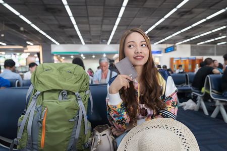 Asian beautiful woman show passport on airport background, holiday vacation travel concepts.