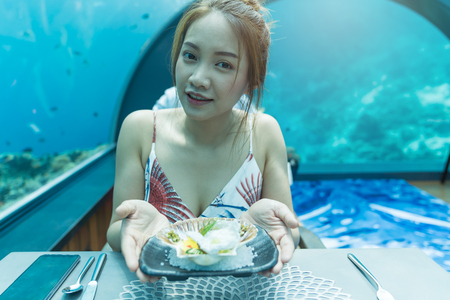 Asian beautiful woman dinner on undersea world background,  underwater restaurants in Maldives. Фото со стока