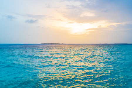 Beautiful tropical Maldives island in the ocean background,  sea with sunset sky for nature holiday vacation background concept.