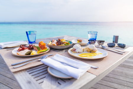 Luxury breakfast food on wooden table, with beautiful tropical Maldives island background, morning time holiday vacation concept.