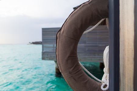 Beautiful tropical Maldives island summer vacation with life ring in luxury resport background.