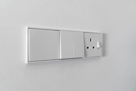 Modern white switch on white wall background. Stock Photo