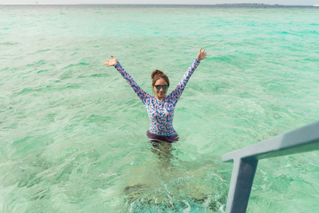 Asian beautiful woman is enjoyful in the lagoon sea background, vacation holiday concepts with tropical Maldives island background.
