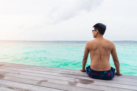 Asian smart man enjoyful traveling sea background, vacation holiday concepts with tropical Maldives island background.