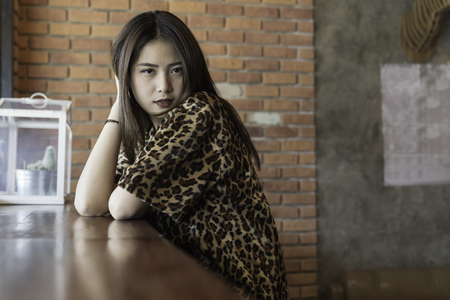 A beautiful woman portrait. Asian teenager concept, with tiger line shirt in the vintage cafe.