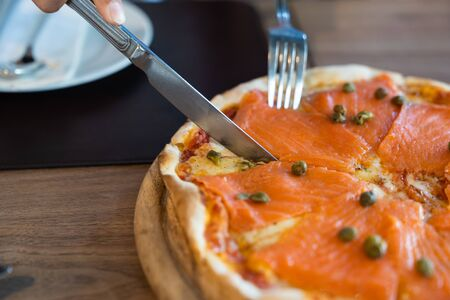 Close up. Full delicious fresh salmon pizzas on wood table, in luxury restaurant, italian pizza food concept. Stock Photo