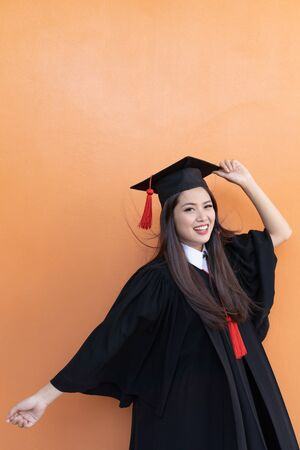 Portrait closeup. Asian beautiful smiley graduate graduated student girl young woman in cap gown on isolated orange background wall. Celebrating graduation ceremony concept.