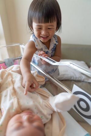 Asian little sister take care her newborn brother. Cute girl and new born baby boy relax inside hospital crib after birth. Toddler kid meeting new sibling. Family with children concept. Love, trust and tenderness