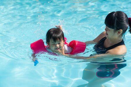 어머니로부터 물속에서 수영하는 아시아의 귀여운 아기 소녀는 수영장에서 돌보고, 수영 수업을 배우는 어린이, 초기 발달 개념 스톡 콘텐츠
