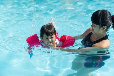 Asian cute little baby girl swimming underwater from mother take care in a pool, child learning to swim lessons and early development concept Stock fotó
