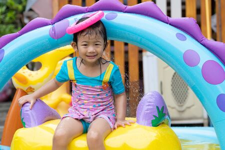 Asian cute girl playing in inflatable baby pool. Kids swim and splash in colorful garden play center. Happy little girl playing with water toys on hot summer day. Family having fun outdoors in the backyard. Stay at home.